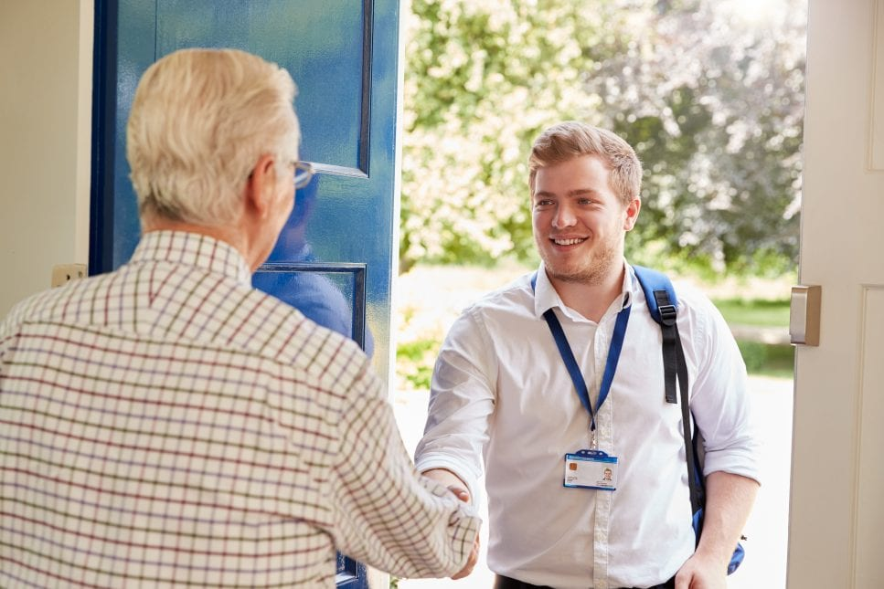 Senior man greeting male care worker making home visit